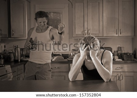 domestic violence with lighting effect - beer-drinking man threatens woman (with bruises) - stock photo