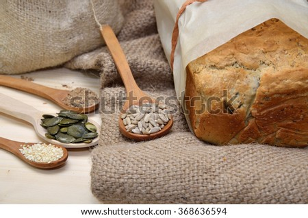 Domestic whole grain bread with spoons of pumpkin, flax, sunflower and sesame seeds on jute cloth - stock photo