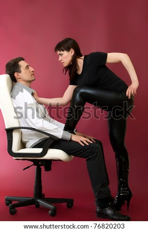 Domination madam and her man on red burgundy background - stock photo