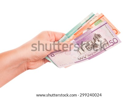 Dominican Republic money in female hand, close-up studio photo isolated on white background