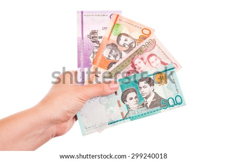 Dominican Republic money in female hands, closeup studio photo isolated on white