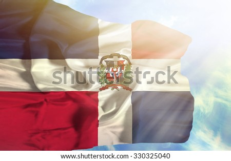 Dominican Republic waving flag against blue sky with sunrays - stock photo