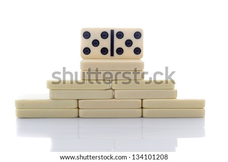 Domino building in the shape of pyramid on white background - stock photo