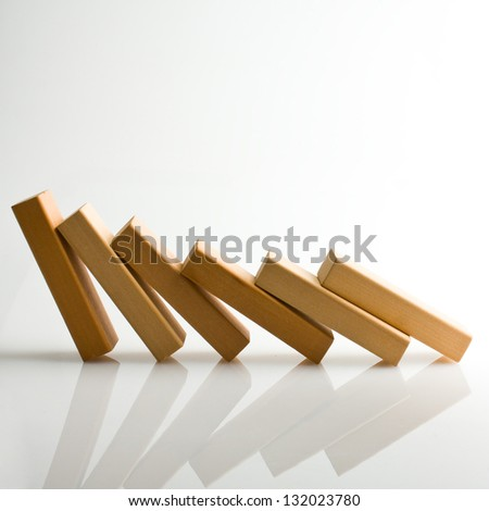 Domino effect - row of white dominoes on white background - stock photo