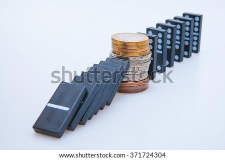 Domino falling on British economy isolated on white - stock photo