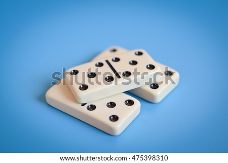 Domino parts, only showing number five over blue table