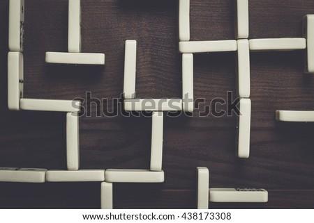 domino pieces maze on dark brown wooden background - stock photo