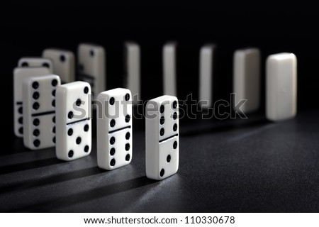 Dominoes lined up ready to fall concept for domino effect, balance and risk - stock photo