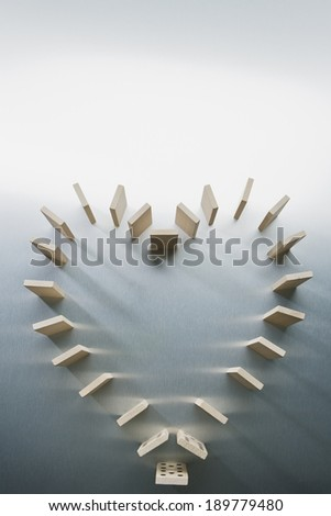 Dominoes standing in heart shape - stock photo