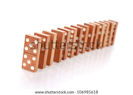 dominos standing in one line isolated on white as an abstract concept - stock photo