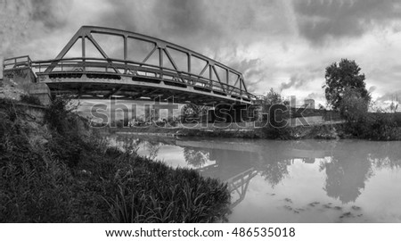 Domos bridge in black and white. Old railroad bridge made of raw steel crossing a river.