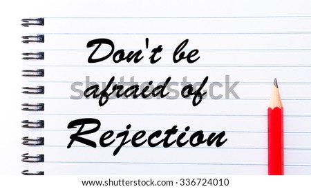 Don't Be Afraid Of Rejection written on notebook page, red pencil on the right. Motivational Concept image