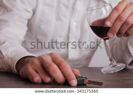 Don't drink and drive concept. Close up of man hand drinking wine and holding car keys. Responsibly and safety driving  - stock photo