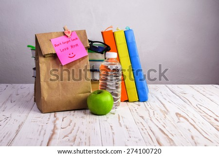 Don't forget lunch , paper lunch bag with apple,water and books on desk with post-it note, - stock photo