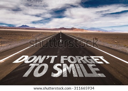 Don't Forget to Smile written on desert road - stock photo