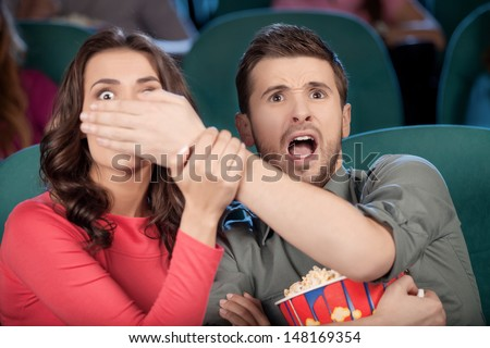 Don't look at this! Shocked young couple watching movie at the cinema while men covering his girlfriend's eyes with hands