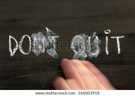 Don't Quit transformed in Do It  message isolated on black background, letters erased by a moving hand. Chalk drawing on blackboard. Business Concept image. - stock photo