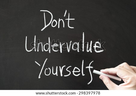 Don't undervalue yourself words written on the blackboard using chalk - stock photo