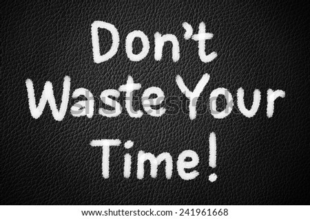 Don't Waste Your Time! written on a black leather texture - stock photo