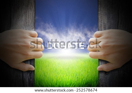 Donate concept. Hand opening an old wooden door and found a texts floating over green field and bright blue Sky Sunrise. - stock photo