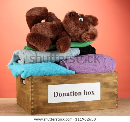 Donation box with clothing on red background close-up - stock photo