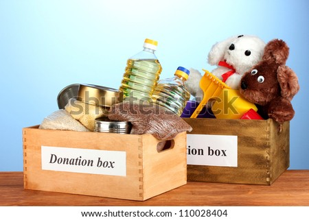 Donation box with food and children's toys on blue background close-up - stock photo