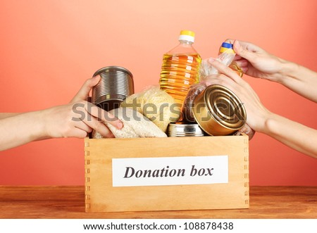Donation box with food on red background close-up - stock photo