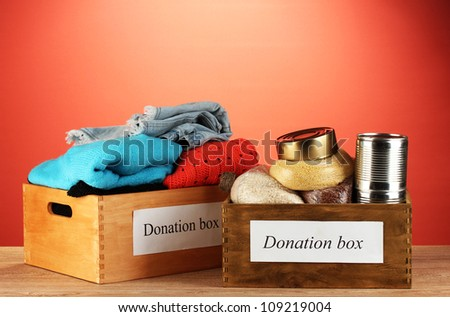 Donation boxes with clothing and food on red background close-up - stock photo