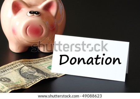 donation or donate concept with piggy  bank on black background - stock photo