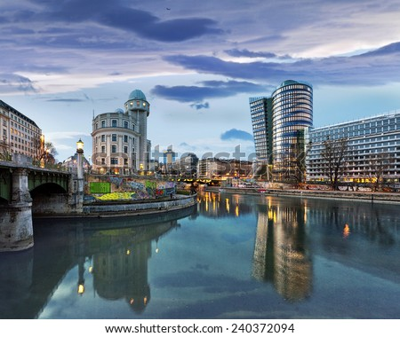 Donaukanal (Danube Canal) of Vienna, Austria. At the right the new UNIQA-Tower and opposite the historic building Urania, a public educational institute and observatory. - stock photo