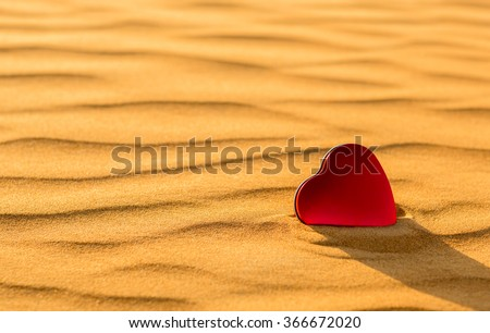 done-Closeup of heart shaped red tin in the golden desert sand. - stock photo