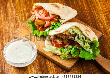 Doner kebab - fried chicken meat with vegetables in pita bread - stock photo