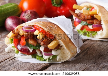 Doner kebab with meat and vegetables in pita bread wrapped in paper close-up on the table and ingredients horizontal  - stock photo