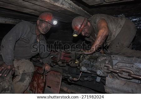 Donetsk, Ukraine - August, 16, 2013: Miners near the coal mining shearer. Mine is named Chelyuskintsev - stock photo