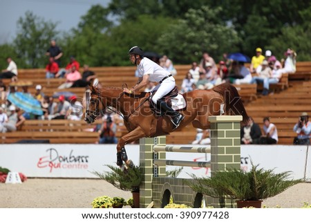 "DONETSK, UKRAINE - JUNE 07, 2009: Gregory Robin overcomes the obstacle at the racehorse in the jumping competition ""Donbass Tour 2009"" CSN** 2 stage on June 07, 2009 in Donetsk, Ukraine."