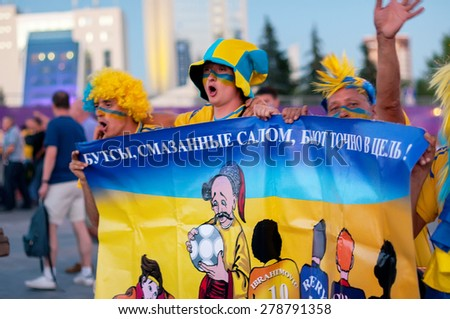 DONETSK, UKRAINE -JUNE 19, 2012: Ukrainian football fans walk near Donbass Arena stadium before EURO 2012  match England vs Ukraine - stock photo