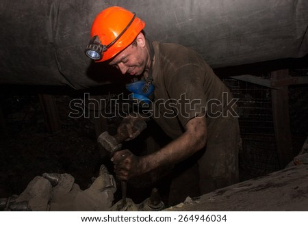 Donetsk, Ukraine - March, 14, 2014: The driver of the coal miner repairs in the underground mine. Mine is named after Abakumov - stock photo