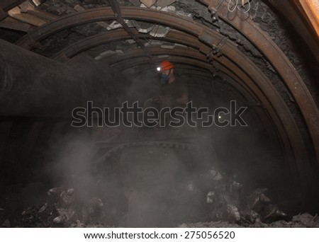 Donetsk, Ukraine - March, 14, 2014: The driver of the coal miner working in a cloud of dust in the underground mine. Mine is named Abakumov - stock photo