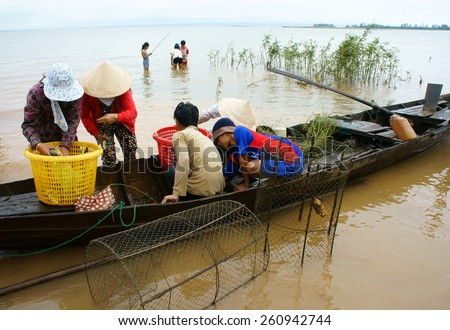 DONG NAI- VIET NAM- AUST 31: Group of Asian fisherman fishing on Tri An lake, a branch of Dong Nai river, crowd of people collect river fish on row boat, Vietnam, Aust 31, 2014