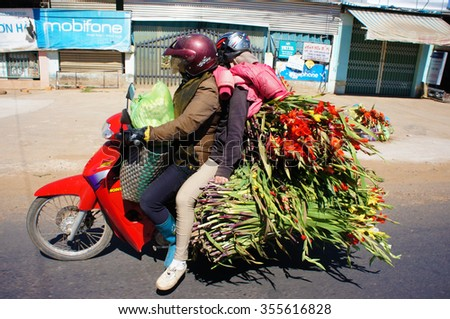 DONG NAI, VIET NAM- FEB 6: Danger traffic on highway, couple transport overload flower and moving on street, insecure situation by vehicle as motorbike increase in spring, Dongnai, Vietnam, Feb 6,2014
