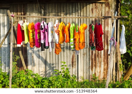 Dong Nai, Vietnam - December 22, 2013: Drying colorful baby's clothes in daylight beside countryside road