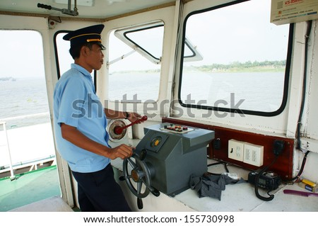 DONG THAP, VIET NAM- JANUARY 27. On cabin of ferry boat, ferryman wear uniform control the wheel to transportation passenger cross the river at Dong Thap, Vietnam, January 27, 2013.