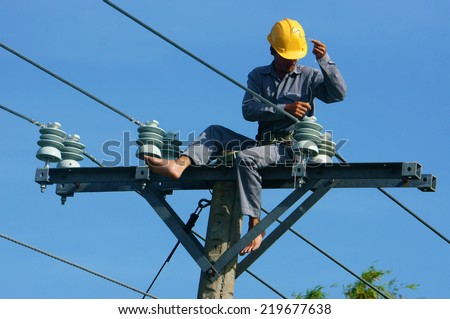 DONG THAP, VIET NAM- SEPT 23:  Asian electrician climb high in pole to work, lineman with cable network, man repair electric post danger and unsafe, is industry service, Vietnam, Sept 23, 2014 - stock photo