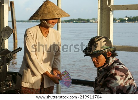 DONG THAP, VIET NAM- SEPT 19: Asian lottery ticket vendor offer Vietnamese man, many poor people earn living by raffle ticket, senior woman work on ferry boat, Vietnam, Sept 19, 2014