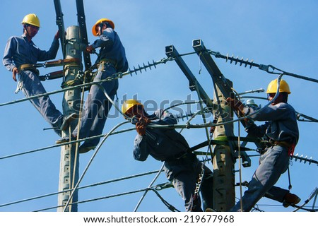DONG THAP, VIET NAM- SEPT 23: Group Asian electrician climb high in pole to work, lineman with cable network, man repair electric post with belt safety, is industry service, Vietnam, Sept 23, 2014 - stock photo