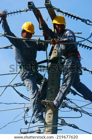 DONG THAP, VIET NAM- SEPT 23: Two Asian electrician climb high in pole to work, lineman with cable network, man repair electric post with belt safety, this is industry service, Vietnam, Sept 23, 2014 - stock photo