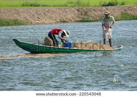 DONG THAP, VIET NAM- SEPT 23: Two Asian farmer work on lake, Vietnamese man feeding, Mekong Delta has many fish pond for fishery, heap of feed on boat, people spread on water, Vietnam, Sept 23, 3014