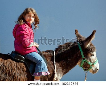 donkey mule with kid little girl riding happy smiling on blue - stock photo