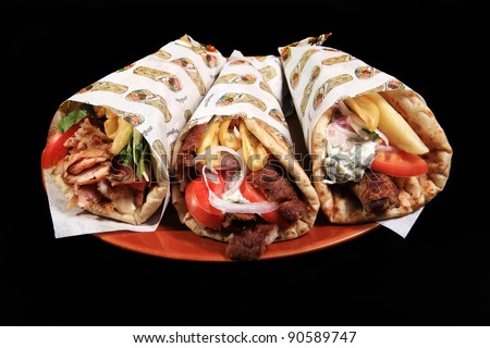 donner kebab served on a plate with pita potatoes and tzatziki sauce isolated on a black background - stock photo