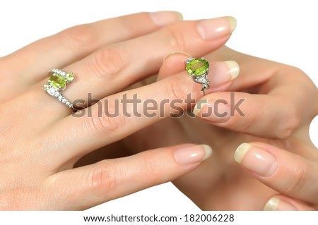 Donning a silver ring with a precious stone peridot ring finger on a beautiful female hand - stock photo